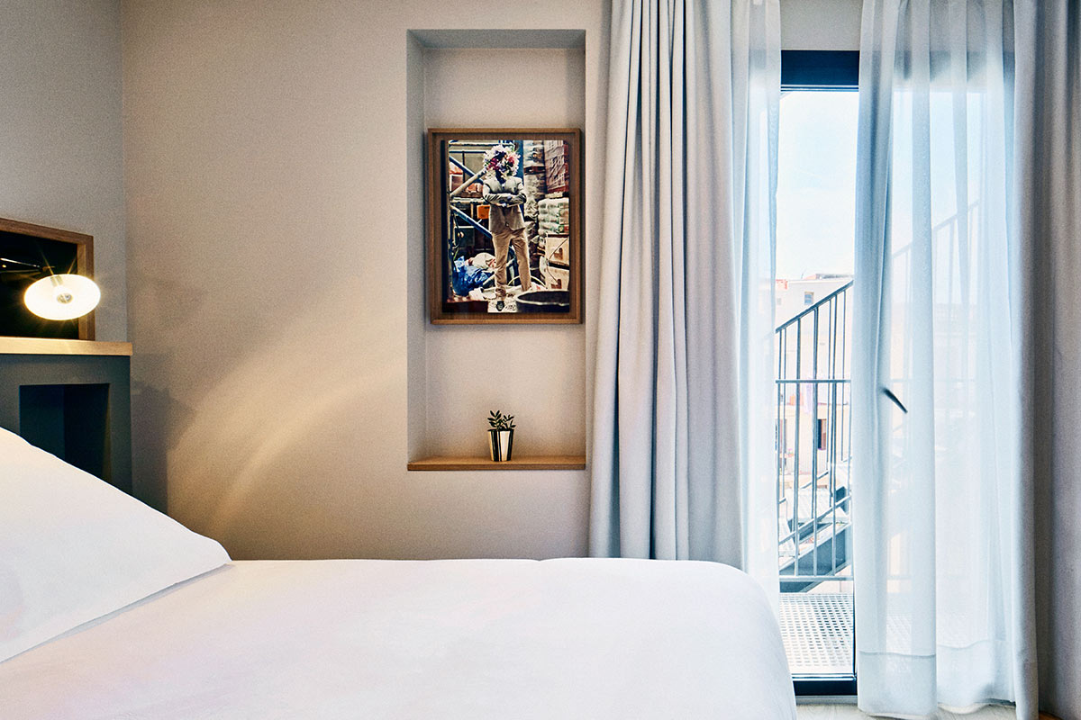 Hotel Brummell, Barcelona - hotel room with bed, hanging painting, floor to ceiling windows, and outdoor staircase