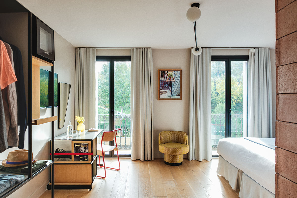 Hotel Brummell, Barcelona - hotel room with open closet, desk, chair, armchair, bed, and floor to ceiling windows