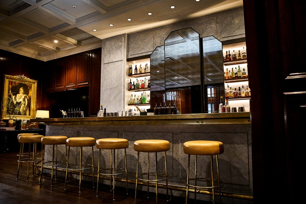 The Adolphus Hotel, Dallas - hotel bar with art-deco mirror, classic bar top, round bar stools, and stocked liquor shelves