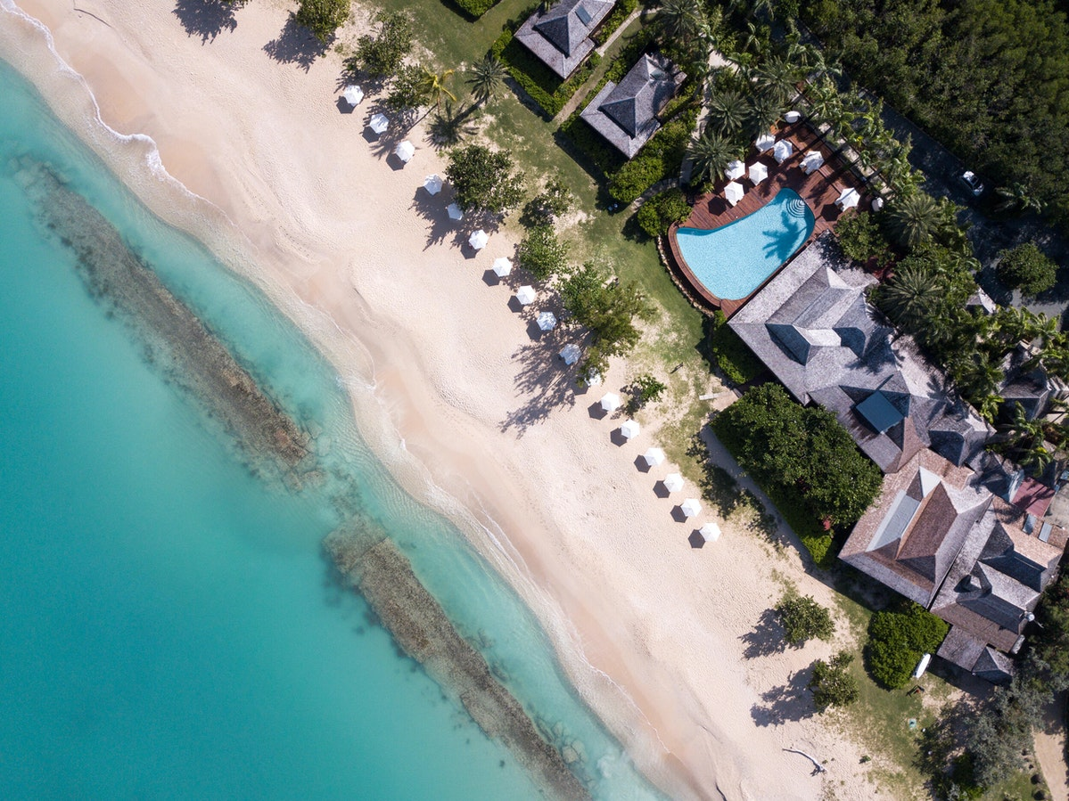 Hermitage Bay, Antigua & Barbuda - birds eye view of resort pool, villas, beach, and Caribbean Sea