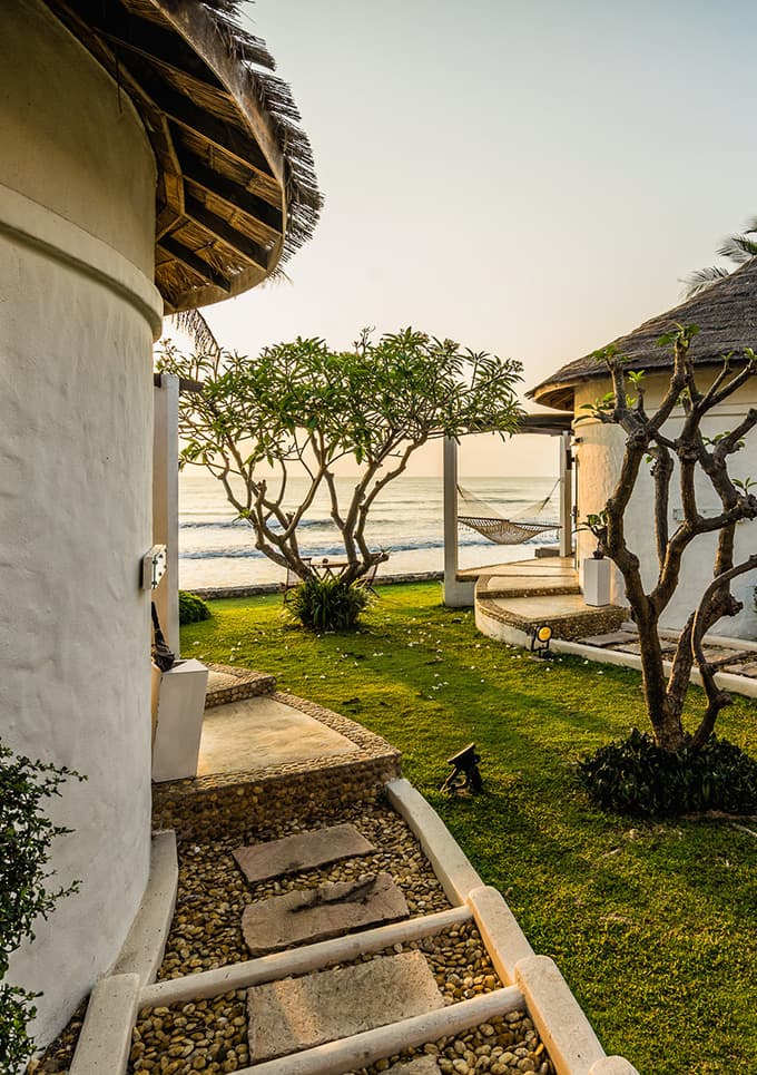 Aleenta Hua Hin Resort & Spa, Pranburi - outdoor bungalows with hammocks and a view of a beach