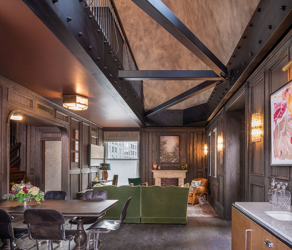 The Beekman, NYC - hotel room with wood walls, steel beams, couch, and table with chairs