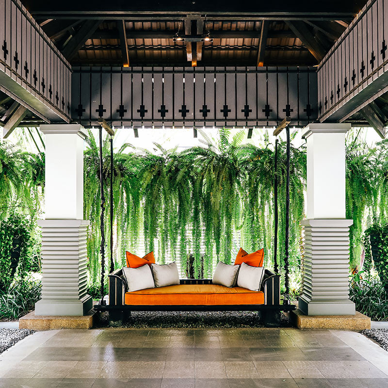 Bensley Collection Shinta Mani, Siem Reap - open air room with a black wood and orange cushion swing in front of plants