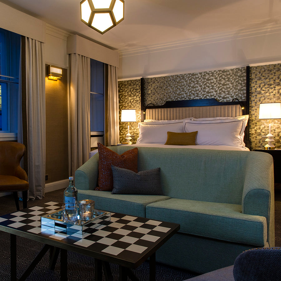 The Academy Hotel, London - hotel room with green sofa, checkerboard coffee table, bed, and golden accent wall