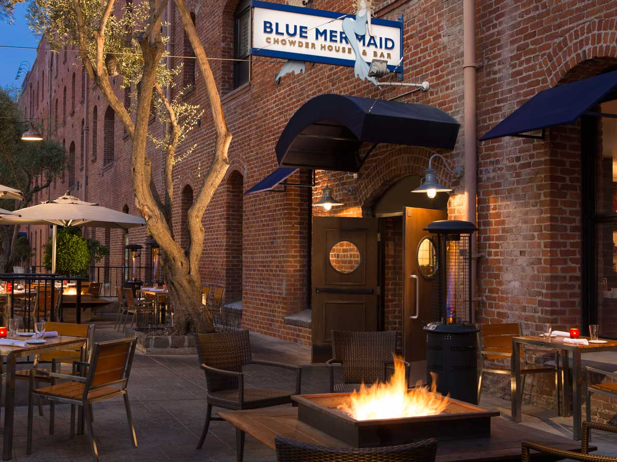 Argonaut Hotel, San Francisco - exterior of Blue Mermaid Restaurant with fire pit and outdoor dining tables at nighttime