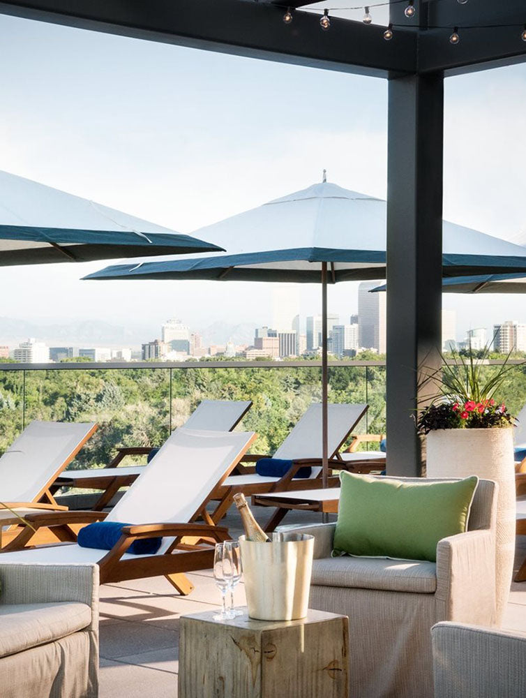 Halcyon, a hotel in Cherry Creek, Denver - rooftop patio with armchairs, lounge chairs, sun umbrellas, and city view