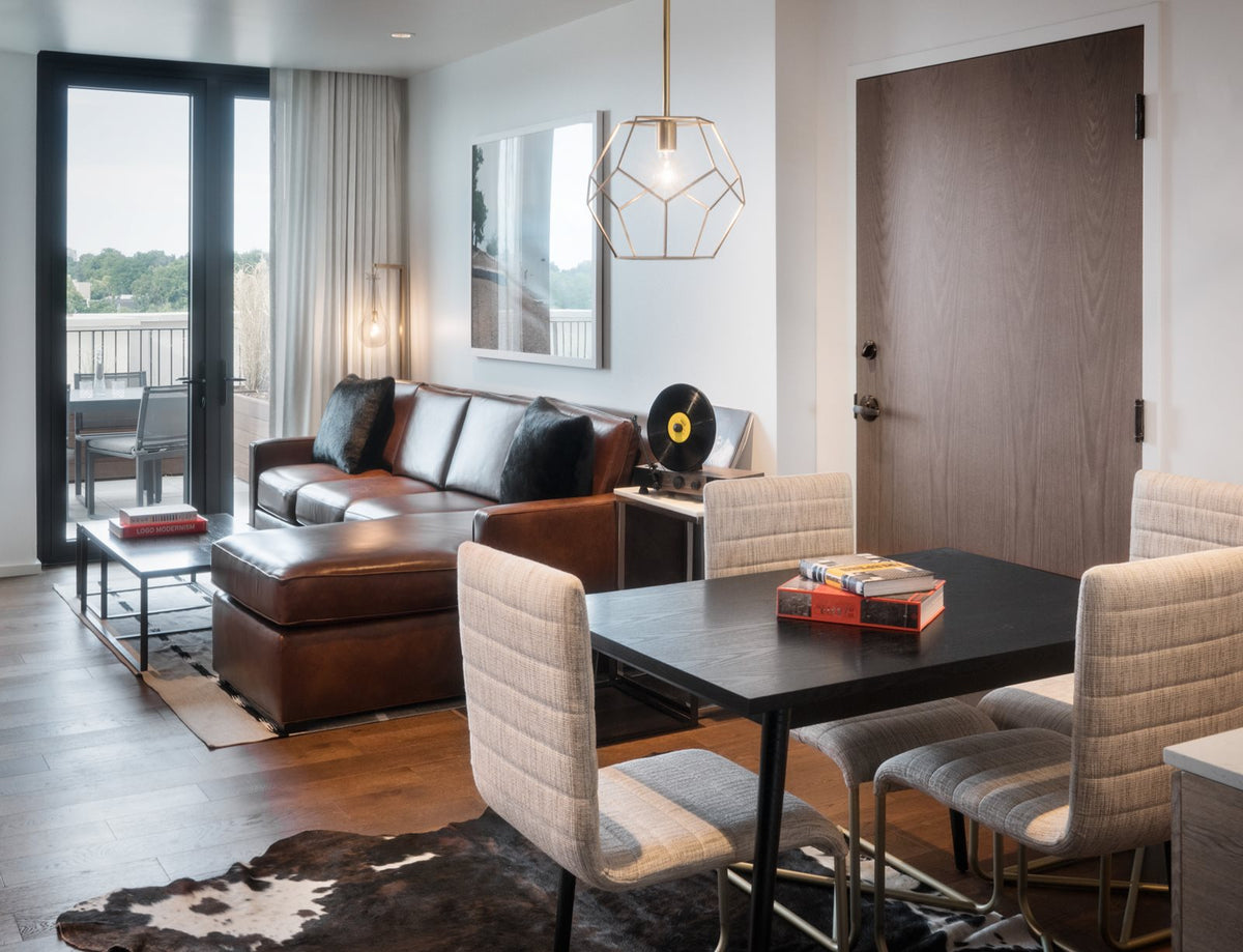 Halcyon, a hotel in Cherry Creek, Denver - hotel room with dining table and chairs, brown leather couch, and access to private balcony