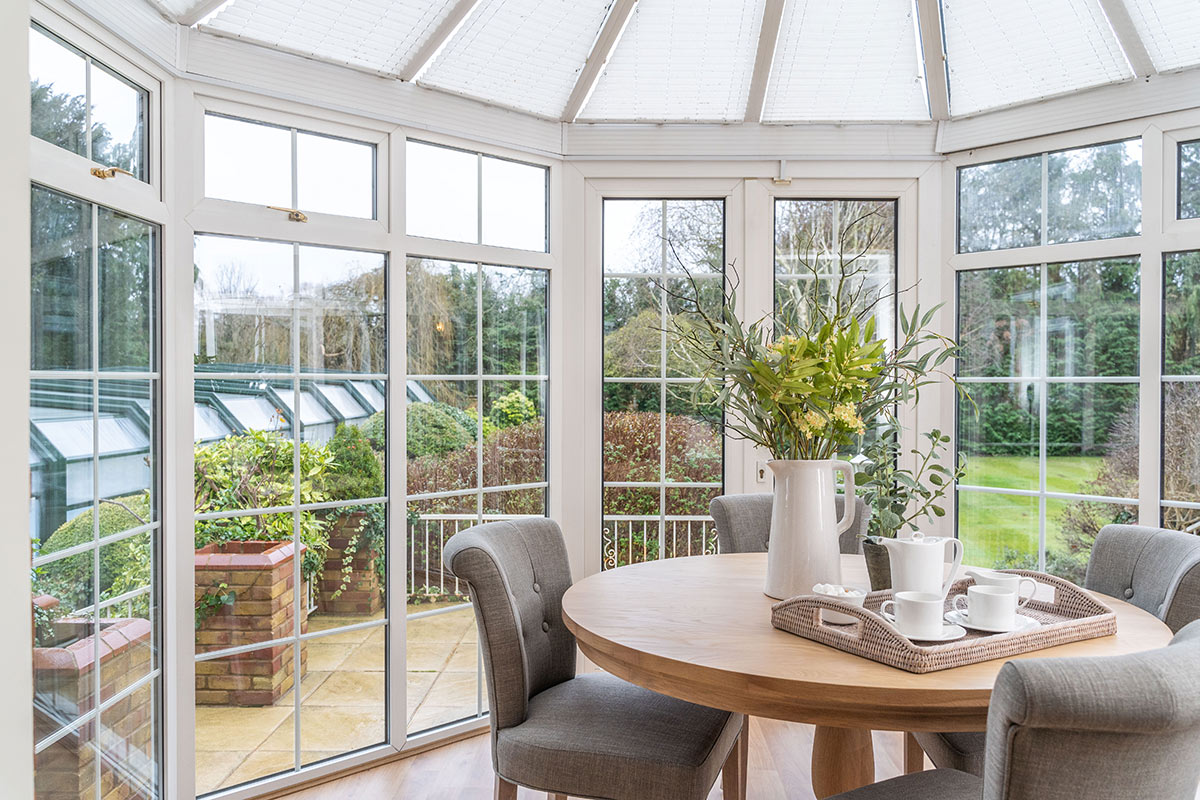 Monkey Island Estate, The Thames-  sun room with table and fabric chairs overlooking garden