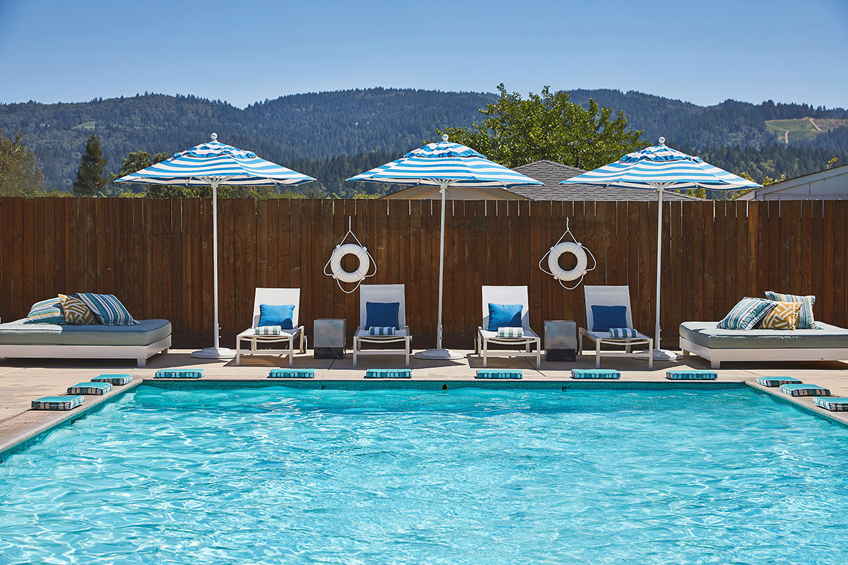 Calistoga Motor Lodge and Spa, Calistoga - hotel pool with lounge chairs, lounge beds, and blue striped sun umbrellas
