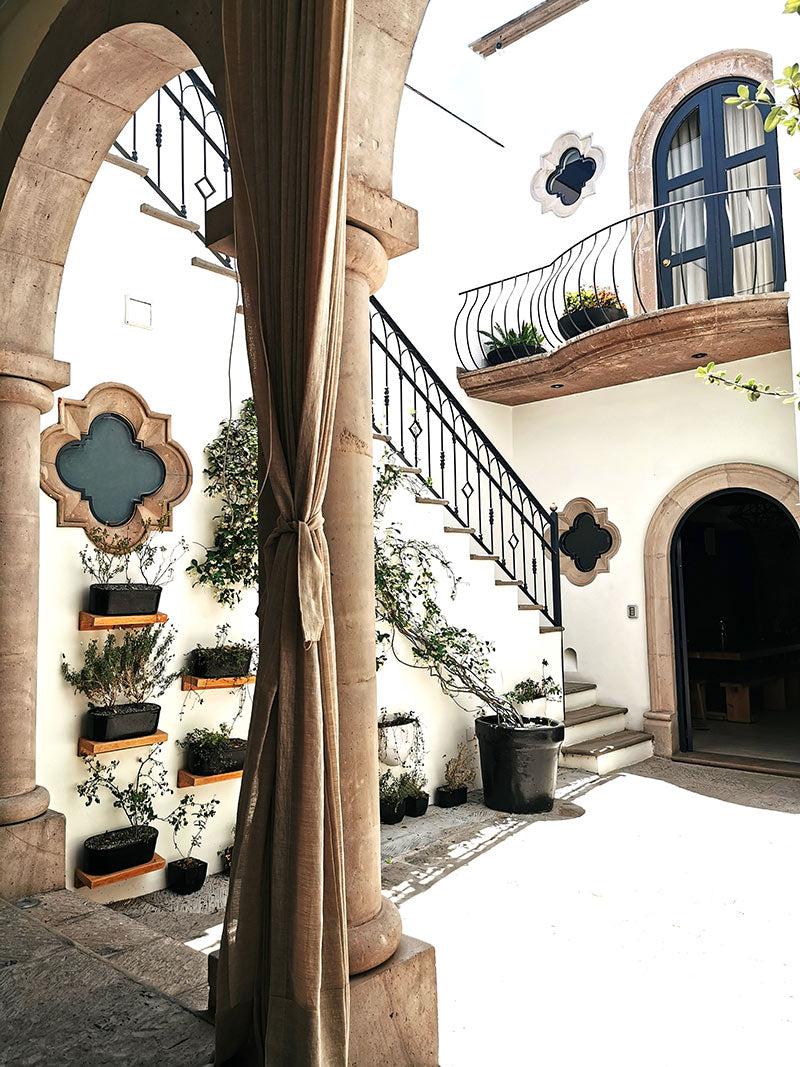 Casa Delphine, San Miguel de Allende - hotel courtyard with iron balconies, white walls, and intricate stone windows