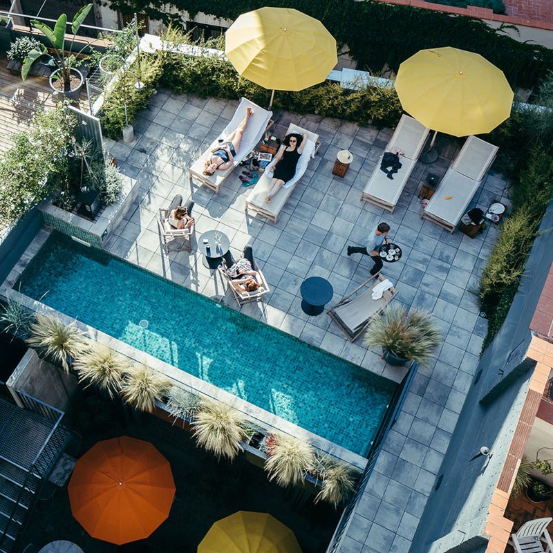 Hotel Brummell, Barcelona - bird's eye view of rooftop pool with yellow sun umbrellas and lounge chairs