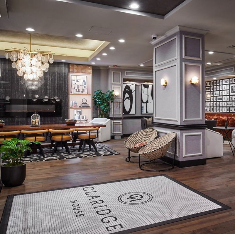 Claridge House, Chicago - hotel lobby with grey and white moulded walls, modern furniture, and stylish contemporary light fixtures