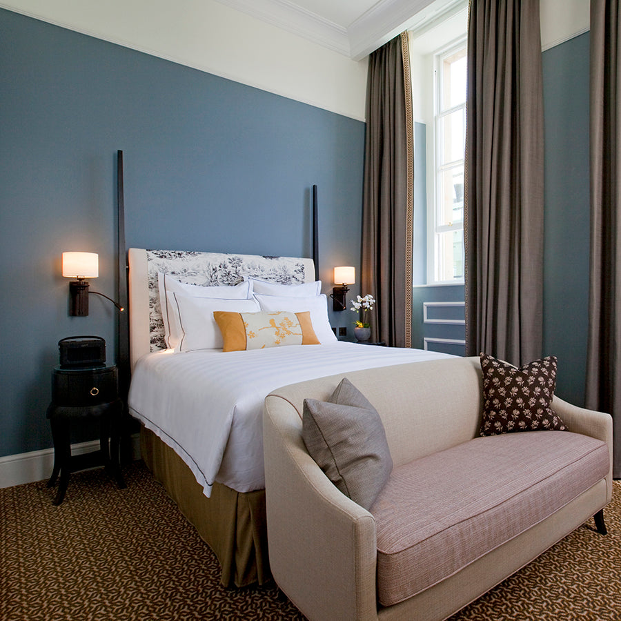 The Gainsborough Bath Spa, Bath - hotel room with powder blue walls, grey curtains and loveseat at foot of bed