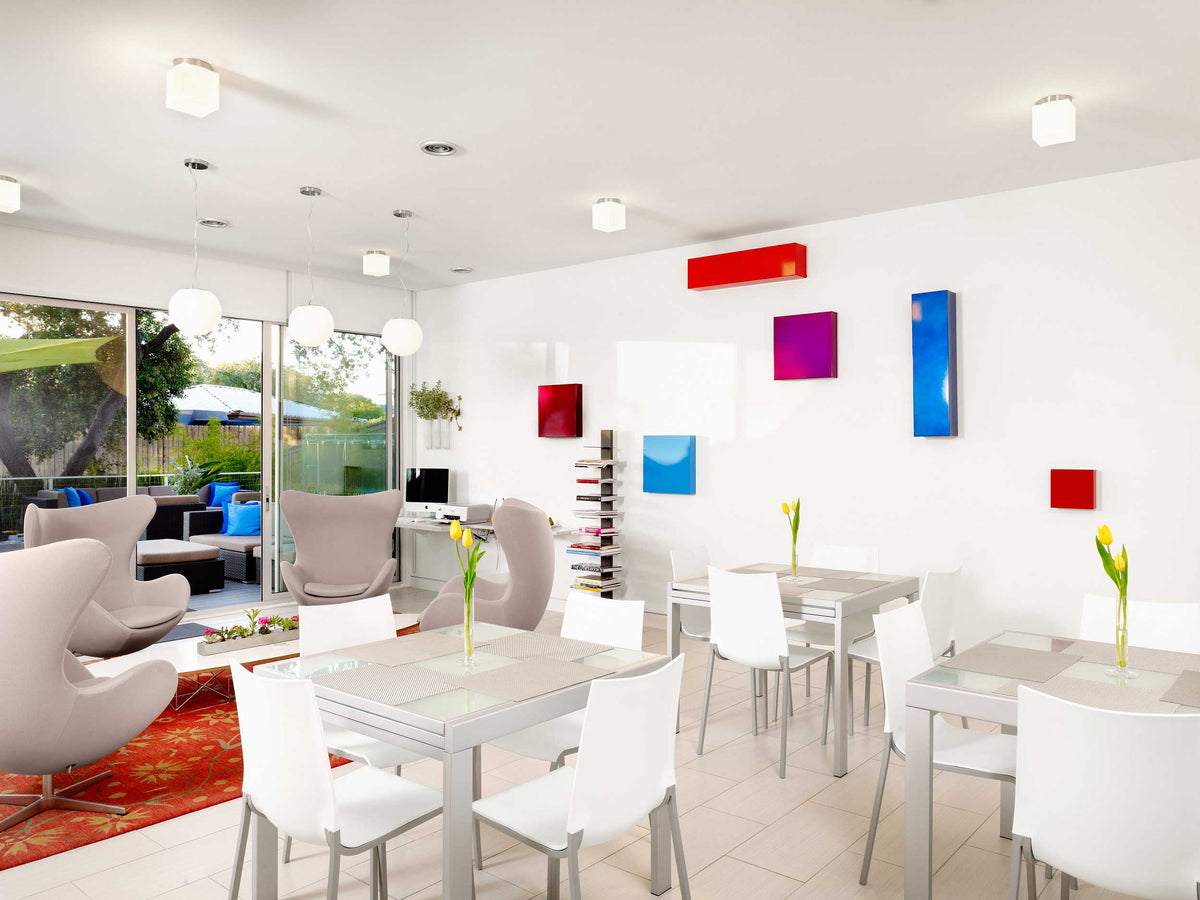 Kimber Modern, Austin - hotel lounge with white furniture, abstract colorful art, and door leading to patio
