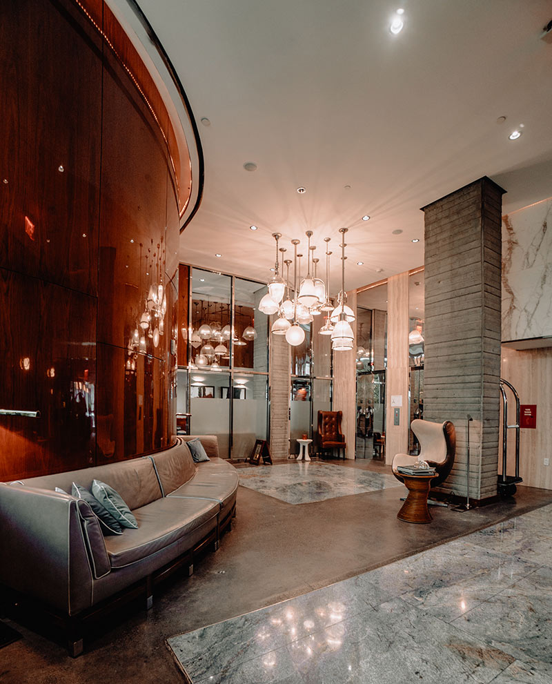Hotel Hugo, NYC - hotel lobby with stone floors and wall accents, a dark wood accent wall, and chic hanging light fixtures