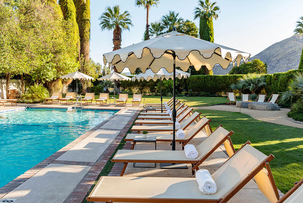 Ingleside Inn, Palm Springs - hotel pool with lounge chairs, sun umbrellas, and mountains in the background