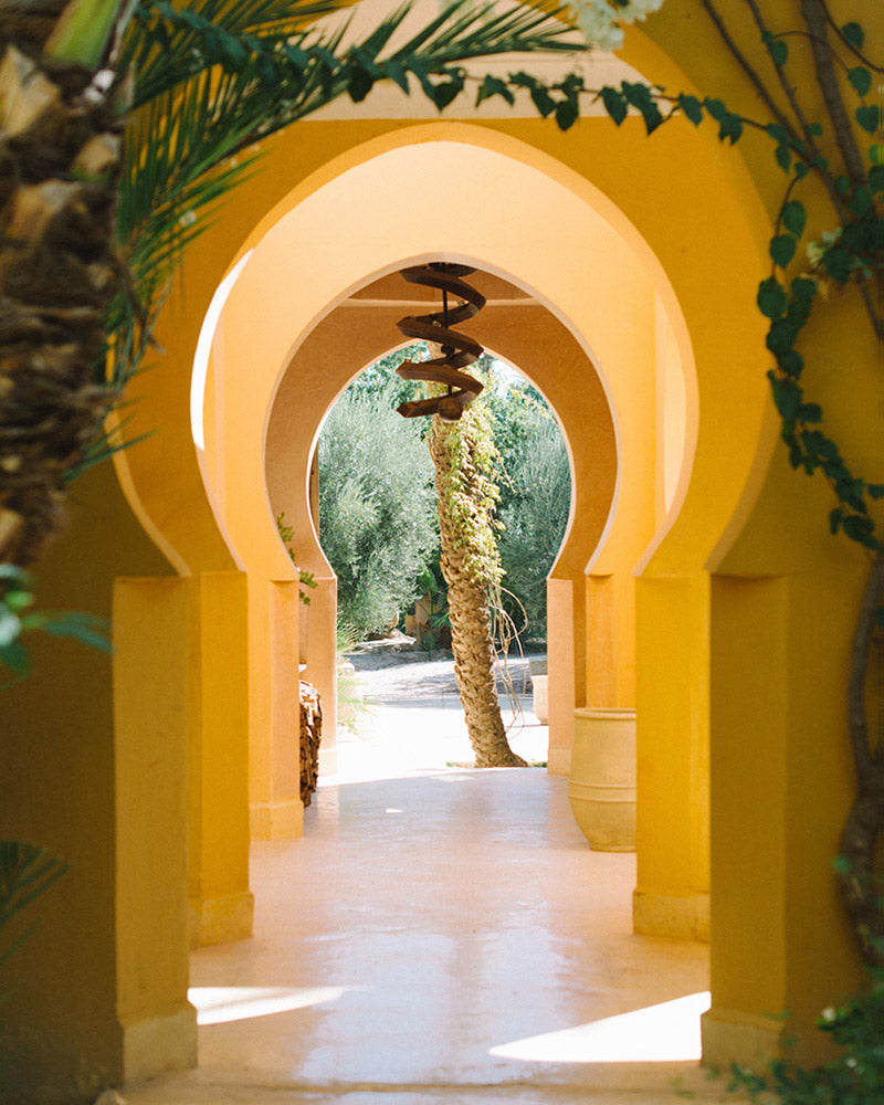 Jnane Tamsna, Marrakech - hallway of yellow Moorish arches leading to a garden