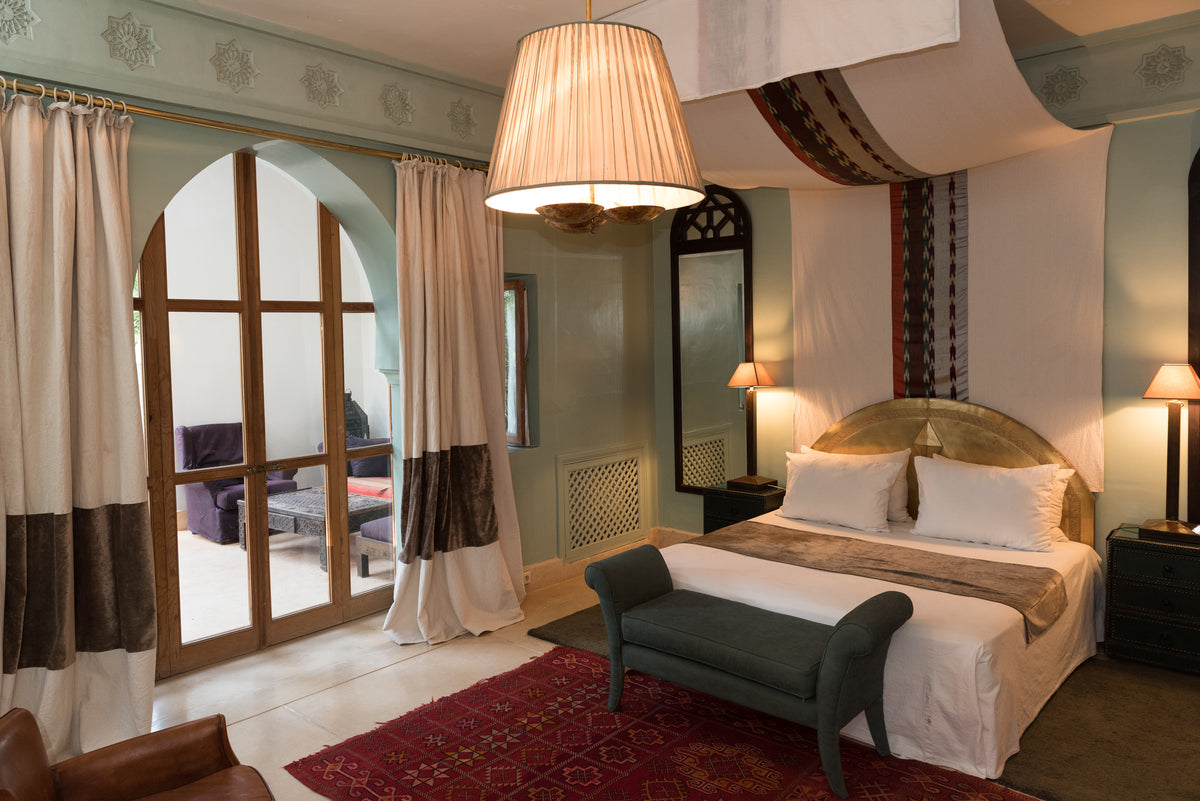 Jnane Tamsna, Marrakech - hotel room with Moroccan design elements and a large keyhole arch door leading to a private patio