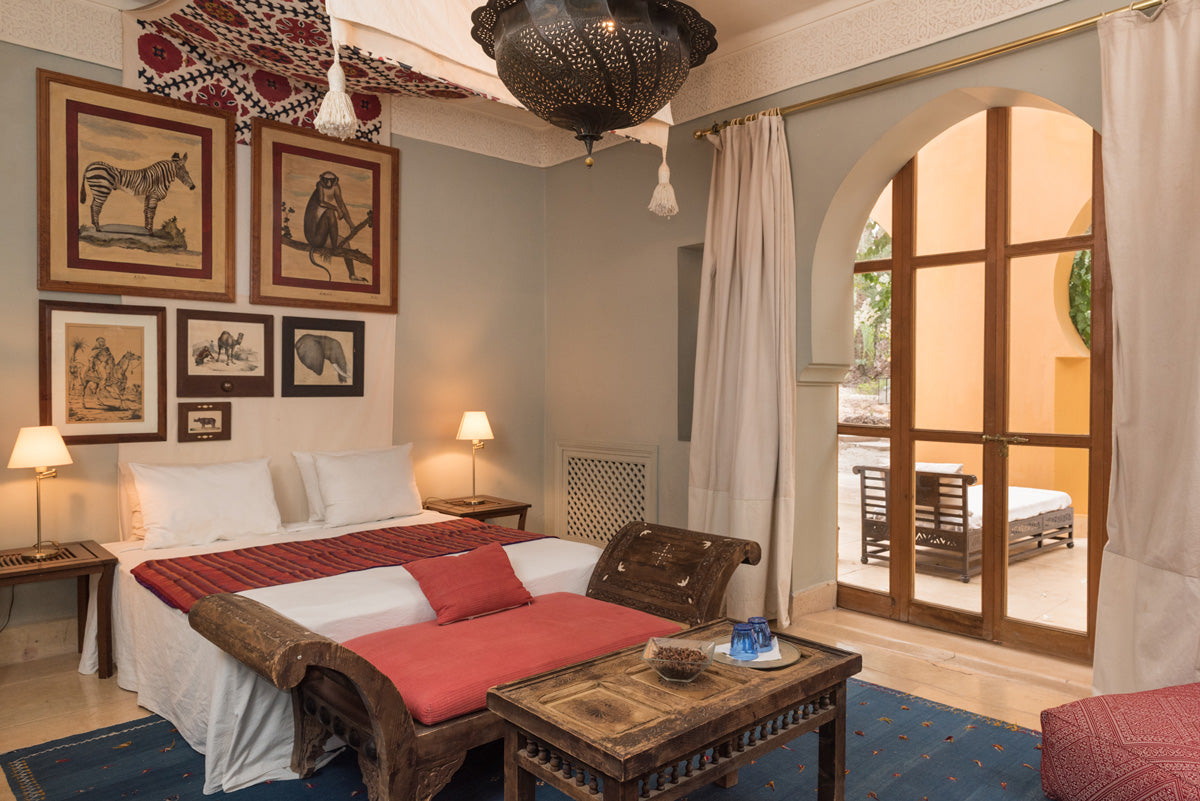 Jnane Tamsna, Marrakech - hotel room with Moroccan design elements, framed animal sketches, and an arch door leading to a patio