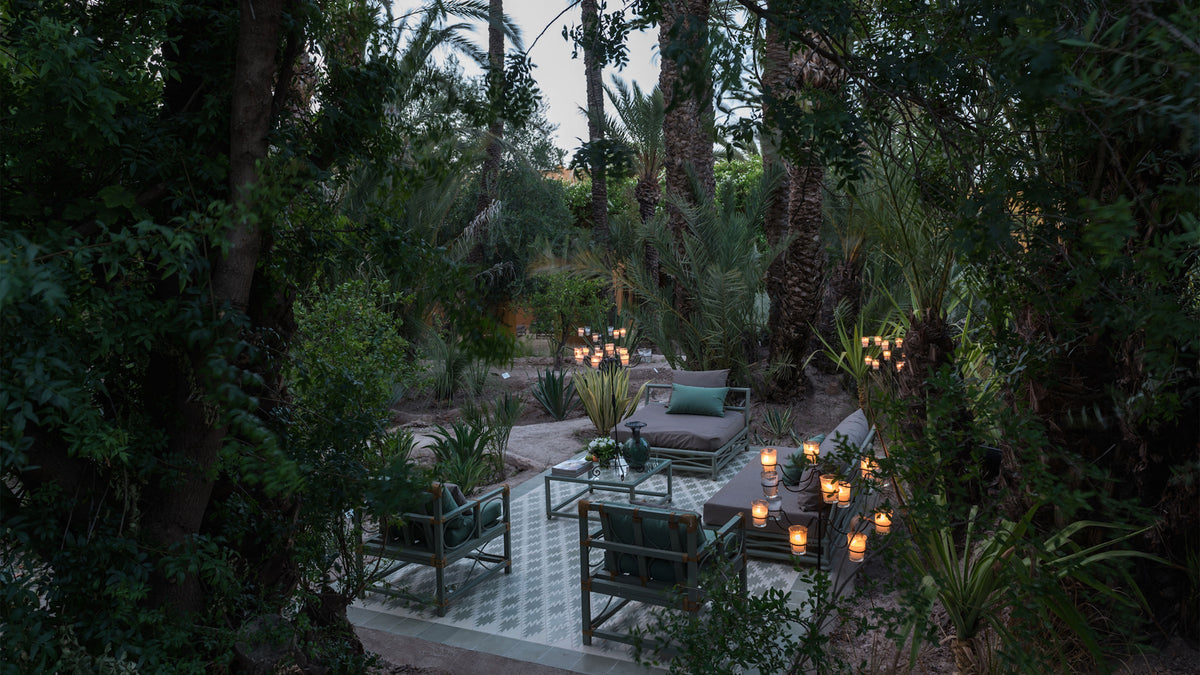 Jnane Tamsna, Marrakech - hotel patio with intricate tiles, armchairs, lounge beds, and large candelabra stands