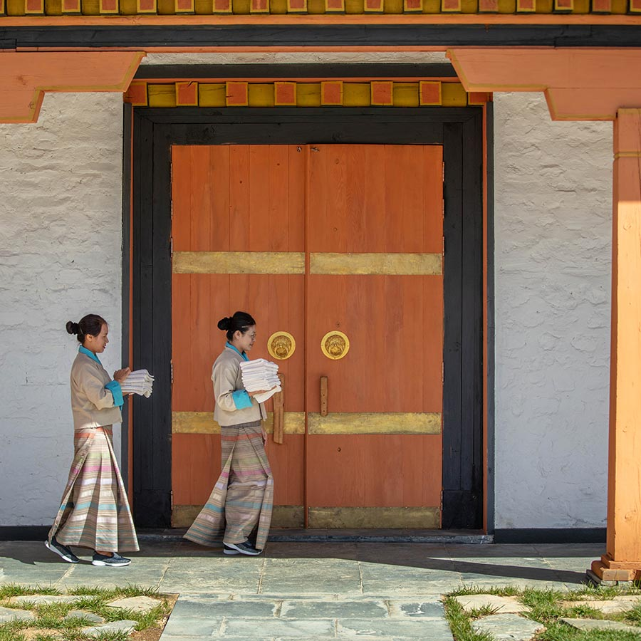 Bhutan Spirit Sanctuary, Bhutan - two hotel workers carry linens in front of a traditional Bhutanese gate