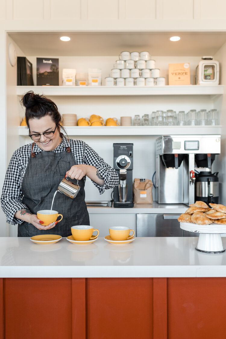 Cuyama Buckhorn, Cuyama - woman pouring steamed milk into a coffee cup at a barista station