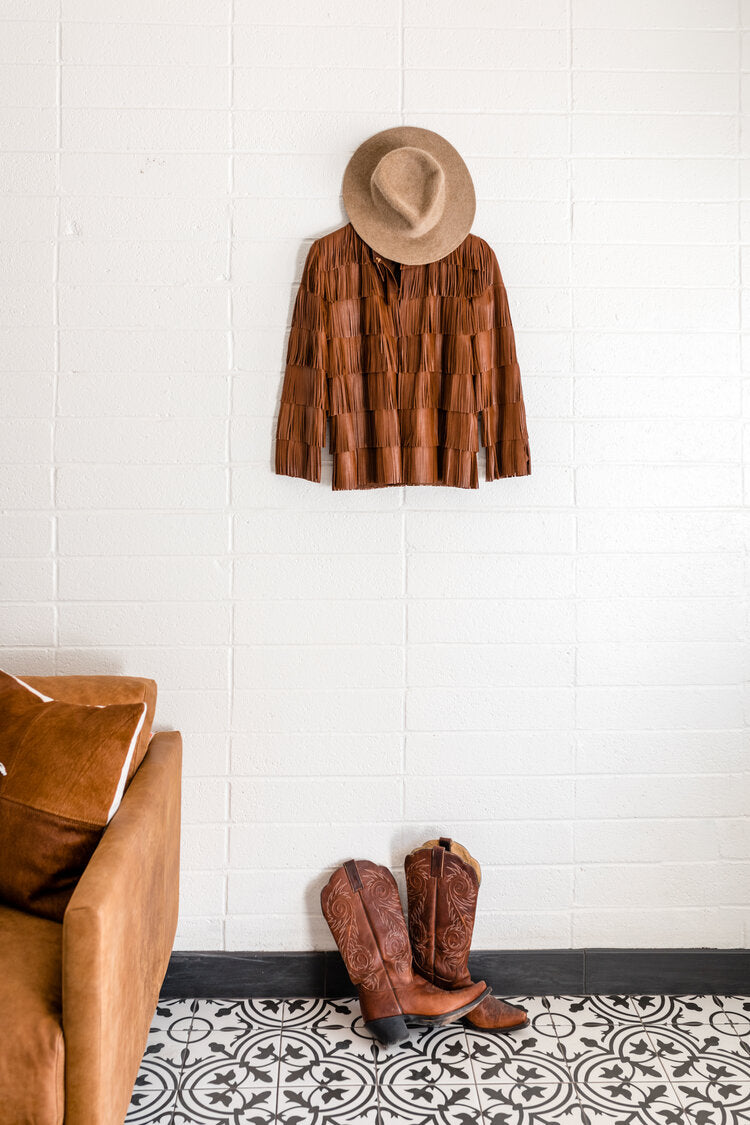 Cuyama Buckhorn, Cuyama - white wall with a fringed brown leather jacket and cowboy hat hanging and cowboy boots on the floor