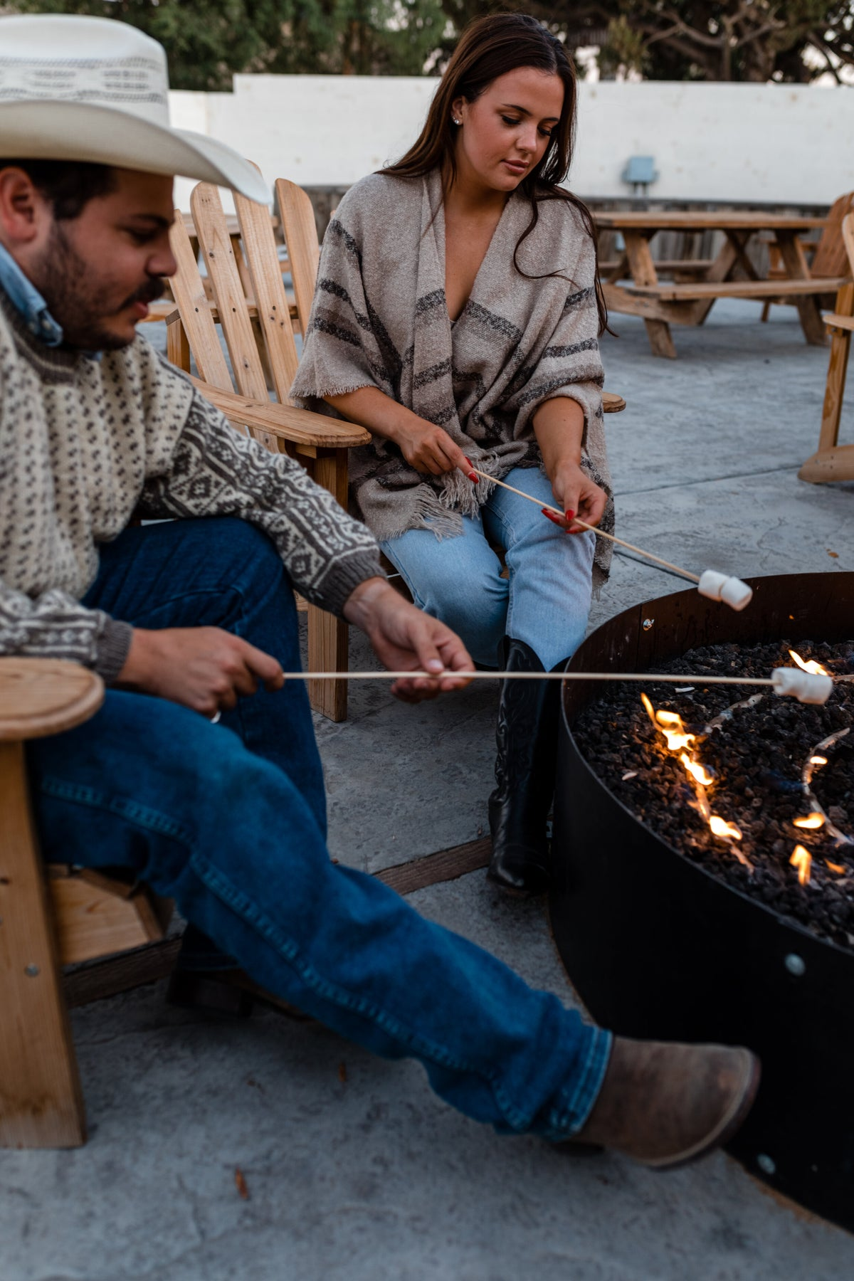 Cuyama Buckhorn, Cuyama - man in a cowboy hat and a woman in a chevron poncho roasting marshmallows over a fire pit
