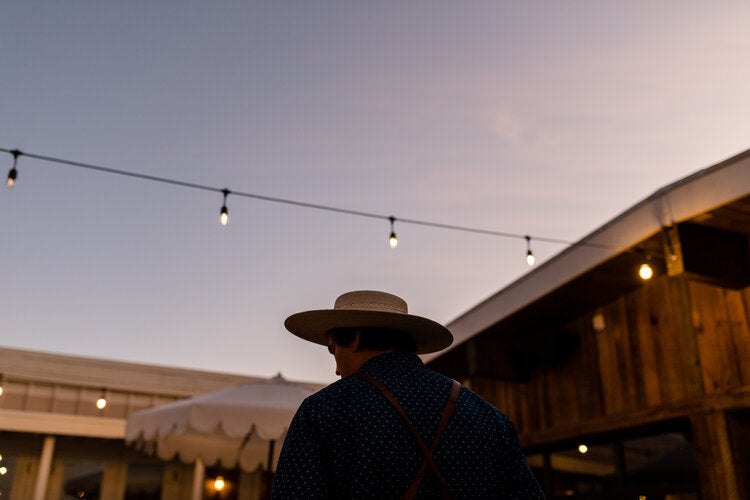 Cuyama Buckhorn, Cuyama -view of a man in a cowboy hat from the back with a patio and string lights in the background at sunset