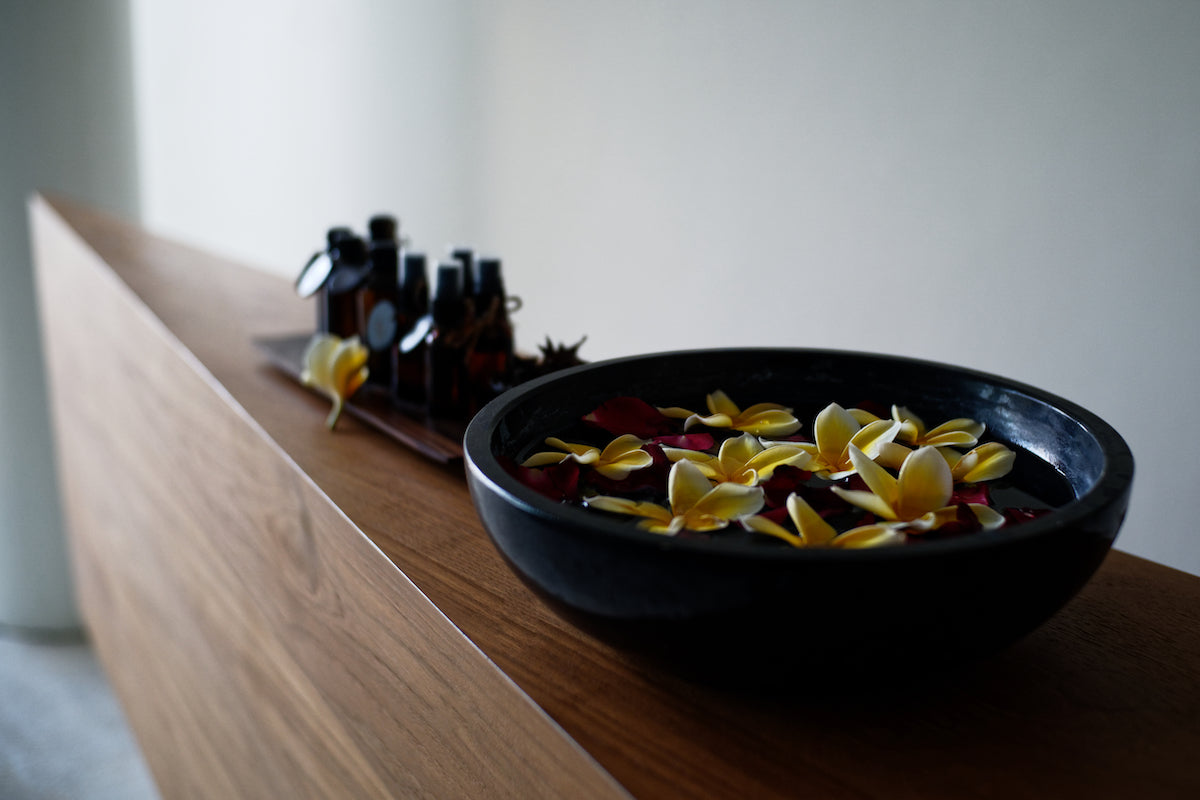 Bisma Eight, Bali - spa with close up on wooden counter with black bowl of water and floating flowers