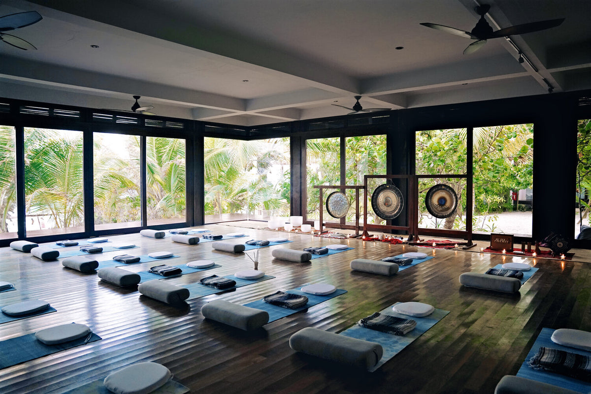 Sanará, Tulum - large open air yoga studio with yoga mats, pillows, and large gongs