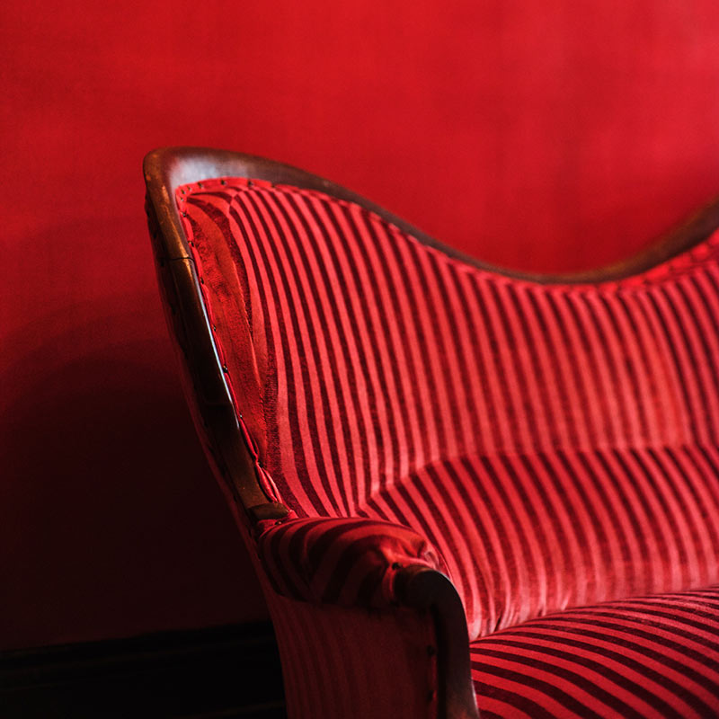 The Columns Hotel, New Orleans - close up of red velvet couch against red wall