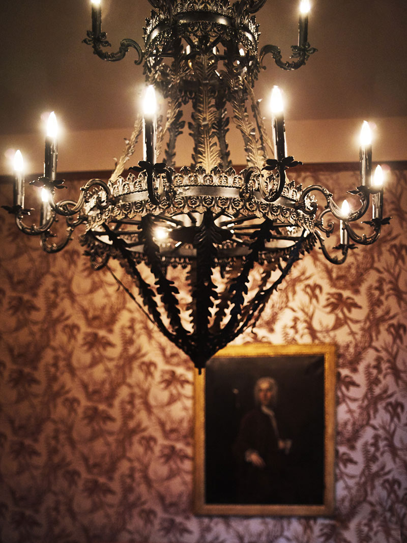 The Columns Hotel, New Orleans - close up of antique metal chandelier and intricate floral wallpaper