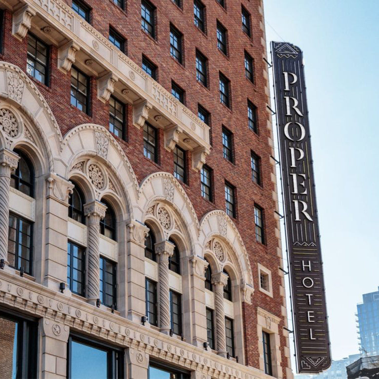 Downtown LA Proper, Los Angeles -exterior of old brick building with stone arches and Proper Hotel light sign