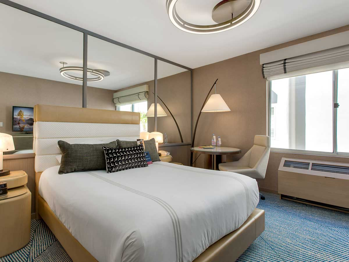 Hotel Zoe Fisherman's Wharf, San Francisco - modern hotel room with a queen size bed, large mirror wall, desk, and chair