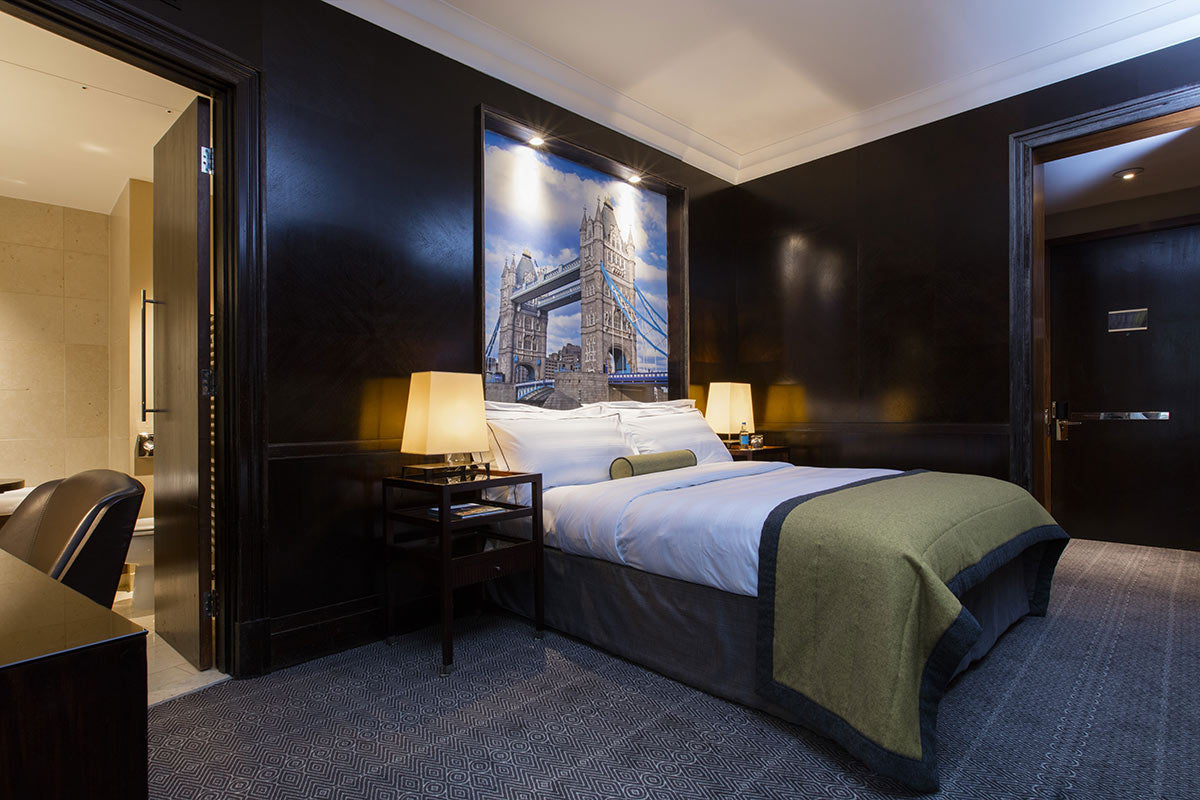 Threadneedles Hotel, London - hotel room with dark mahogany walls, bed, desk, chair, and door leading to stone tiled bathroom