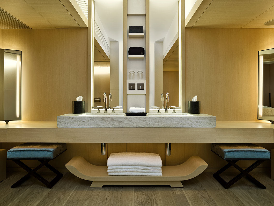 The Upper House, Hong Kong - hotel bathroom with tall vanity mirrors, double sink vanity, folded towels, and 2 stools