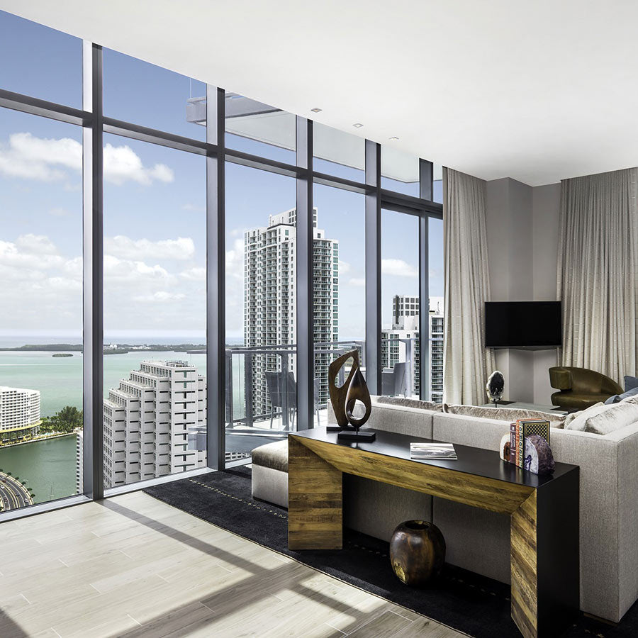 EAST, Miami - hotel room with couch, tv, desk, and floor to ceiling windows showing a city and an ocean