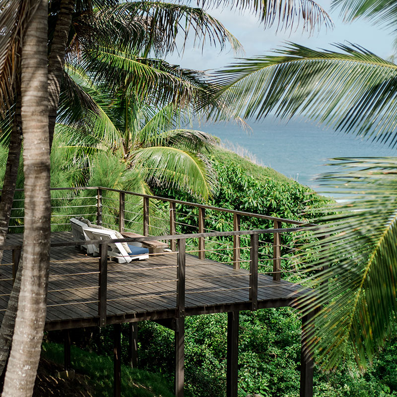 ECO Lifestyle + Lodge, Barbados - rustic wooden elevated patio over jungle plants overlooking ocean