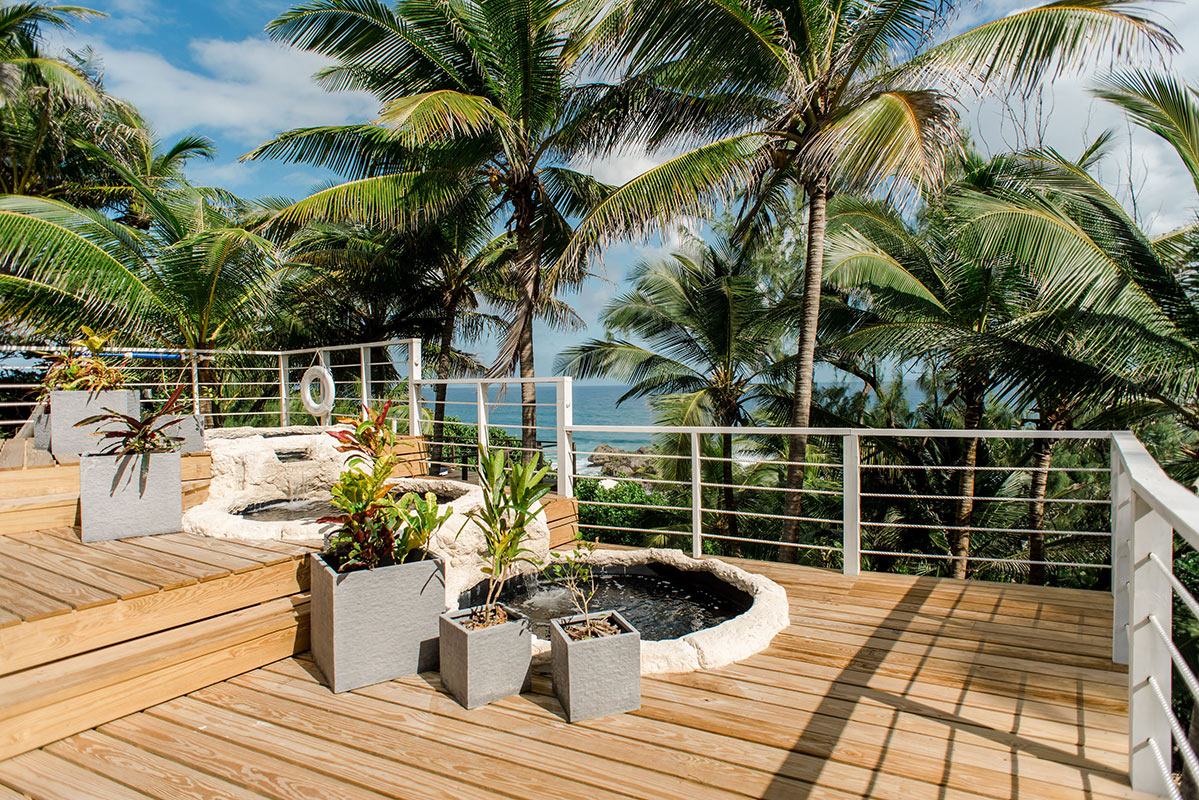 ECO Lifestyle + Lodge, Barbados - hotel patio with rock waterfall, plants in planters, and palm trees overlooking ocean