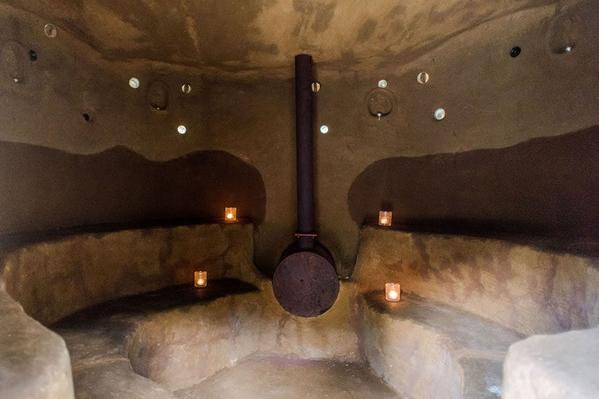 ECO Lifestyle + Lodge, Barbados - rustic sauna with clay interior and seating, candles, and traditional heater