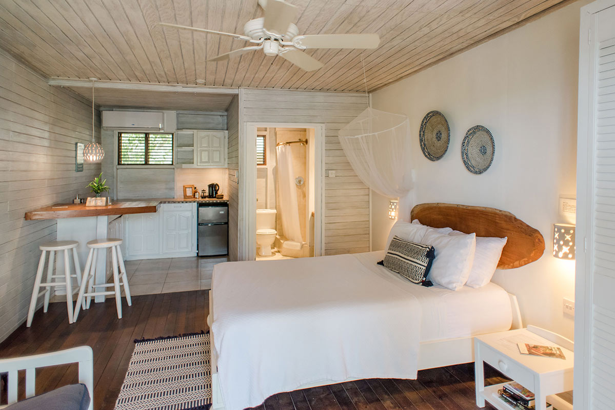 ECO Lifestyle + Lodge, Barbados - rustic hotel room with bed, mosquito net, small kitchen, and bathroom