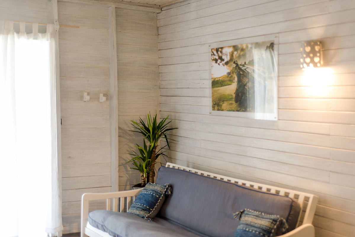 ECO Lifestyle + Lodge, Barbados - hotel room with white pine board walls, couch, and potted plant