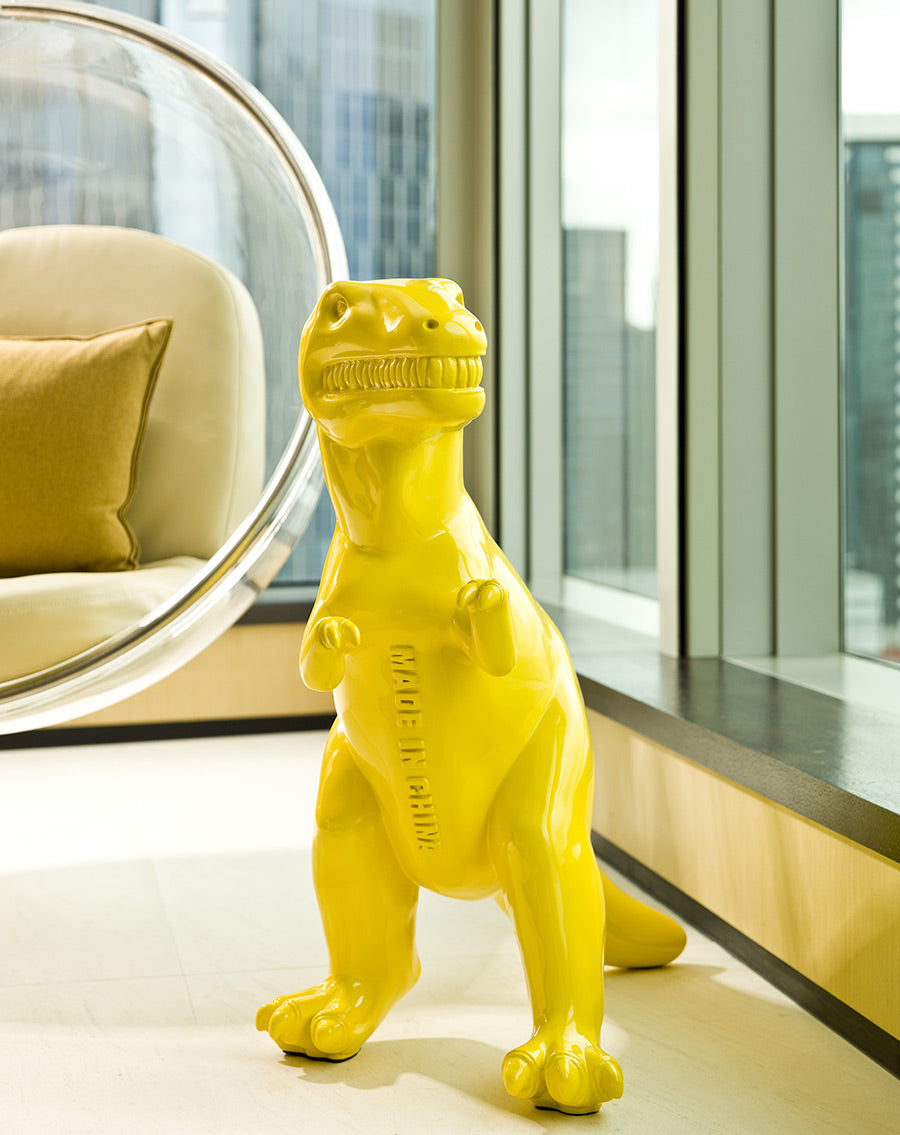 EAST, Hong Kong - close up of a small yellow dinosaur statue with a hanging chair and windows with a city view in the background