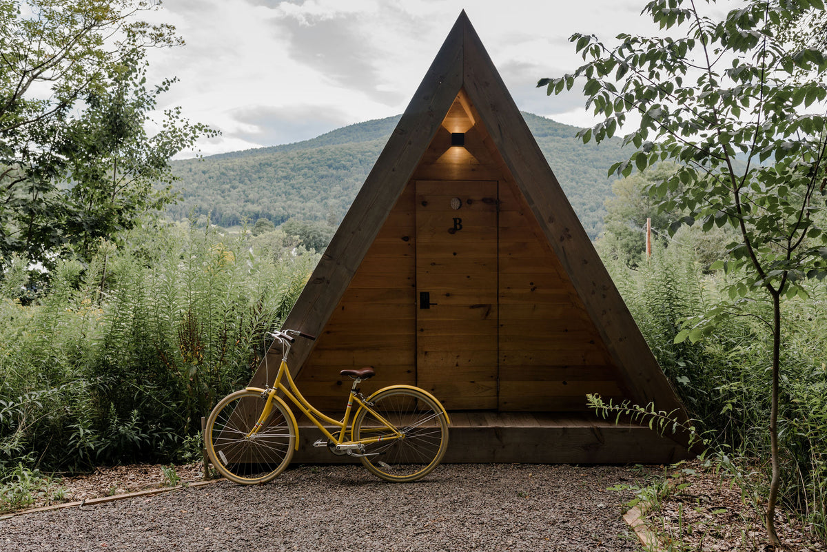 Eastwind Hotel & Bar, NY - private hotel bungalow, triangular natural wood structure with a yellow bicycle in the front