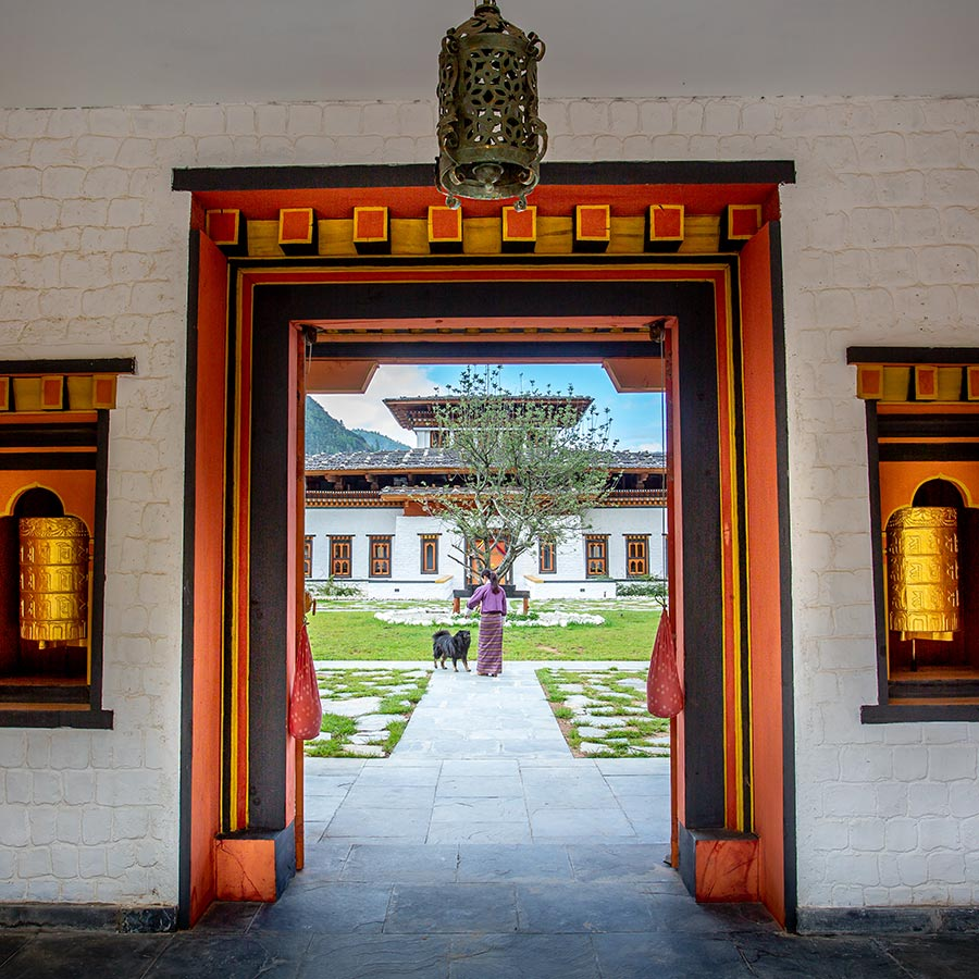 Bhutan Spirit Sanctuary, Bhutan - view of hotel courtyard through large traditional red and gold Bhutanese gates