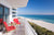 Faena Hotel, Miami Beach - hotel room balcony with red tiki chairs overlooking white beach and blue ocean