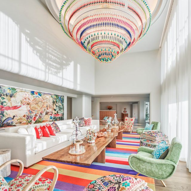 Faena Hotel, Miami Beach - colorful hotel lobby with a long white couch, long wooden coffee table, and green armchairs
