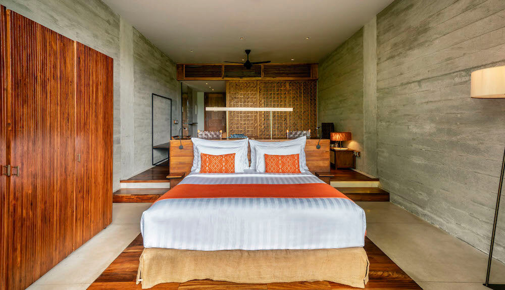 Bisma Eight, Bali - hotel room with stone walls and wooden accents and a large bed in the center of the room