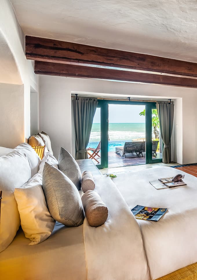 Aleenta Hua Hin Resort & Spa, Pranburi - hotel room with a king size bed and sliding doors leading to a patio and a beach